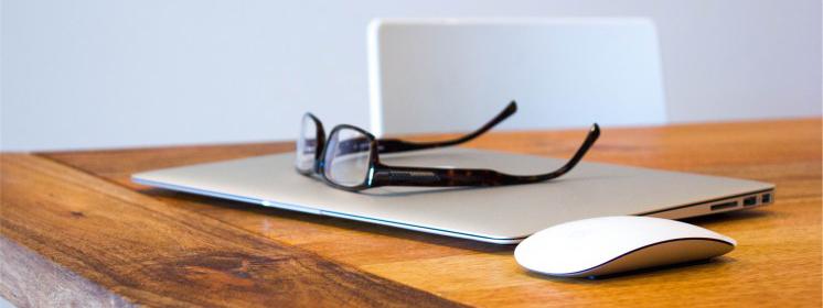 Laptop Maus und Brille auf dem Tisch