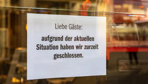 Schild mit Hinweis auf Schließung am Eingang eines Geschäfts